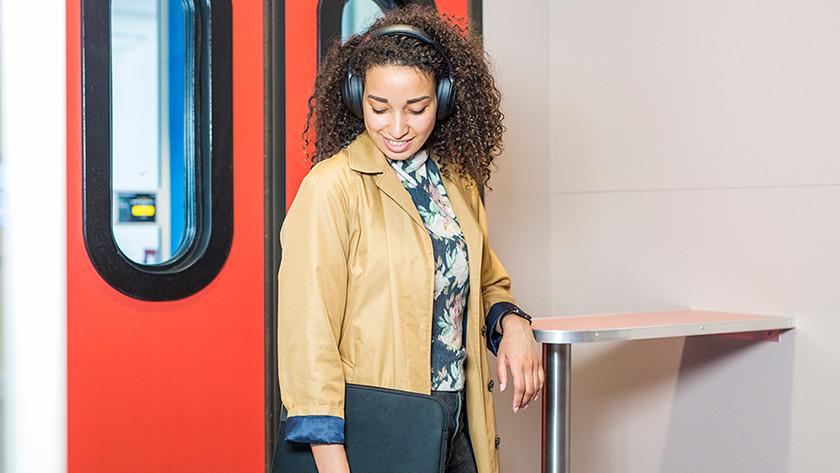 Vrouw in trein met noice cancelling koptelefoon