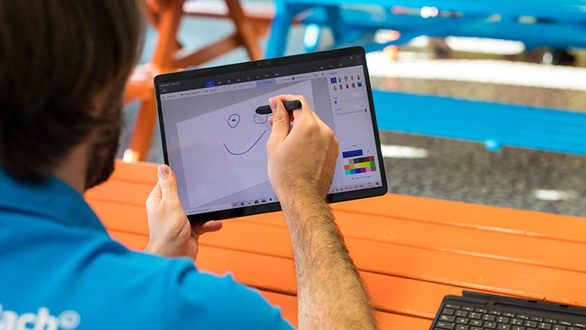 Man tekent gezicht op Surface laptop in tabletmodus.