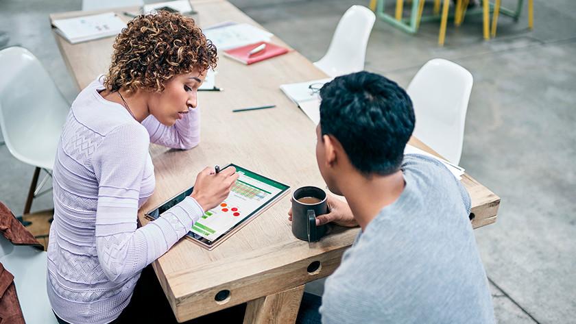 Twee mensen overleggen op Windows 10 laptop achter een tafel.