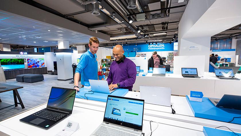 Klant probeert laptop in Coolblue winkel terwijl medewerker meekijkt.