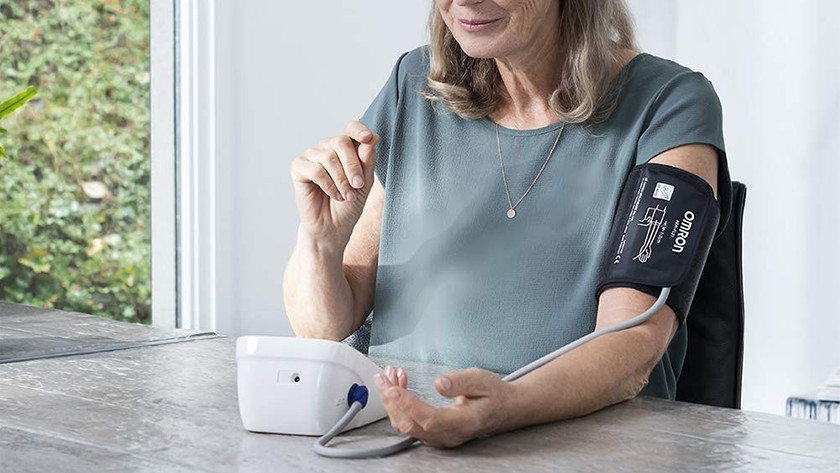 Vrouw met bloeddrukmeter om bovenarm