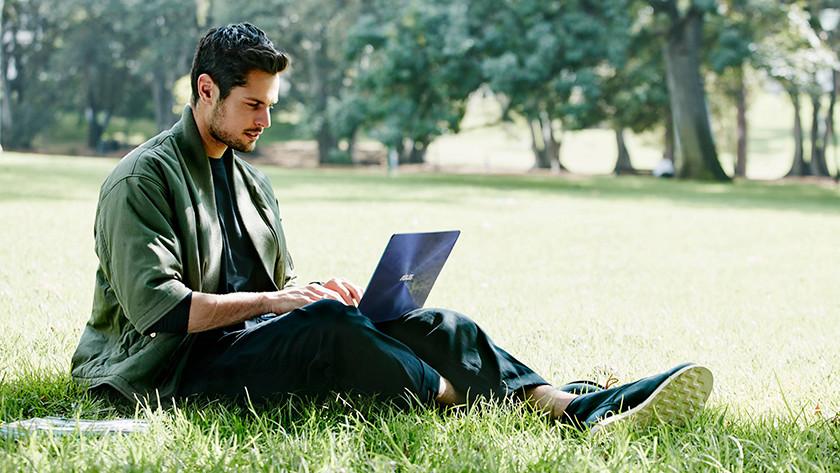 In het gras zittende man werkt in park op Asus laptop.