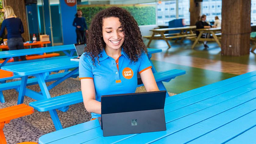 Vrolijk meisje werkt achter Surface Pro laptop op blauwe picknicktafel.