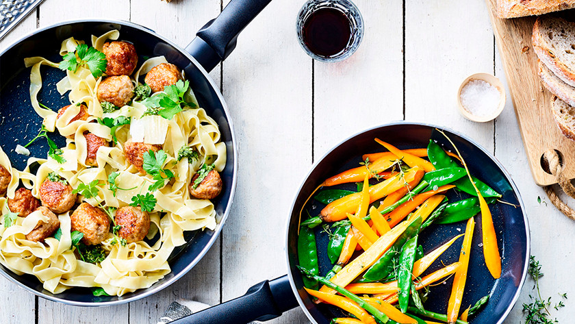 Ceramic pan with pasta, meatballs, and vegetables