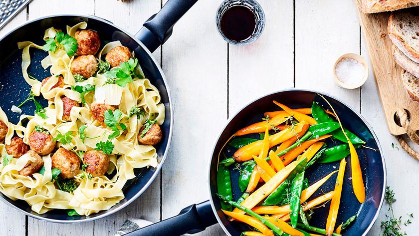 Keramische pan met pasta, gehaktballen en groenten
