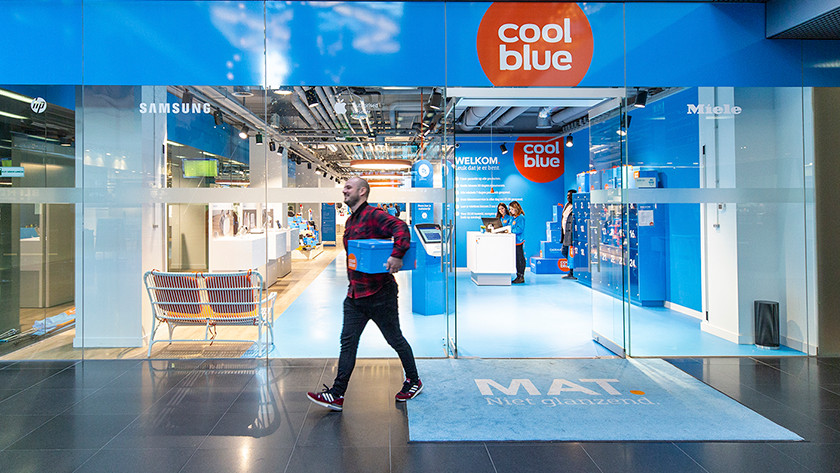Man walks out of Coolblue store with Coolblue box under his arm.