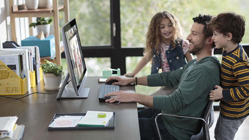 Homme avec deux enfants assis à son bureau, travaillant derrière son ordinateur tout-en-un.
