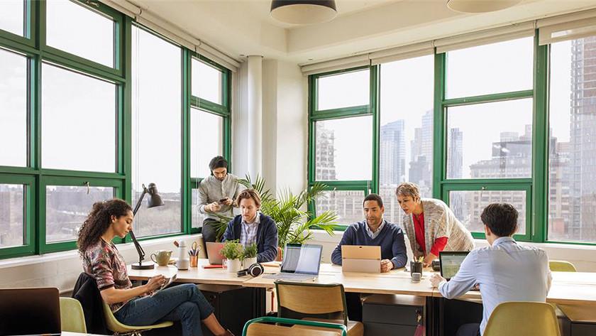 Verschillende mensen werken samen achter een bureau op kantoor.