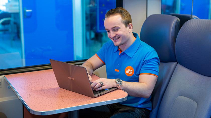 Un homme souriant dans un train travaille sur un ordinateur portable Asus.