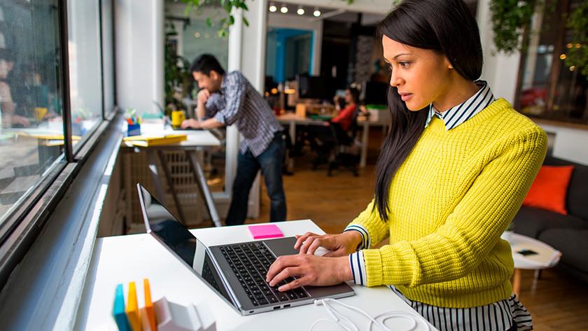 Vrouw in gele trui werkt op laptop.