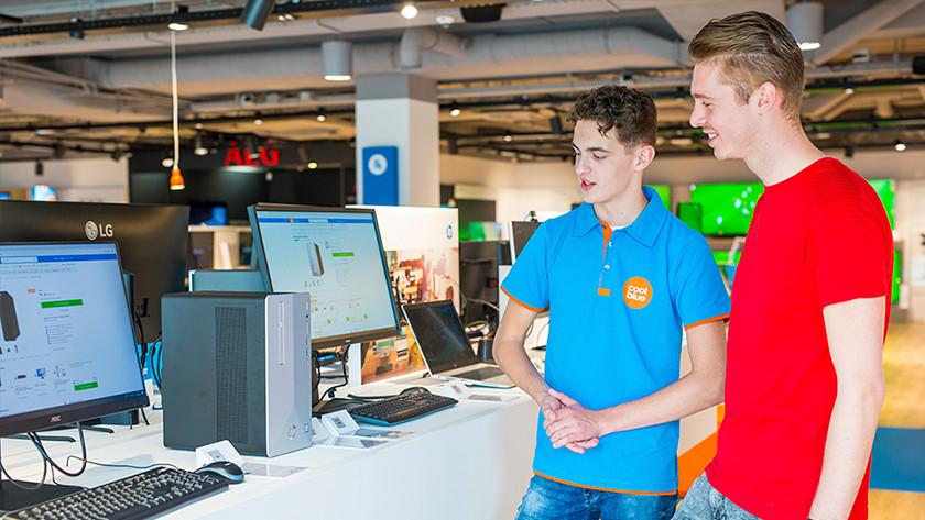 Coolblue winkelmedewerker adviseert klant in winkel met voetbal op de achtergrond.