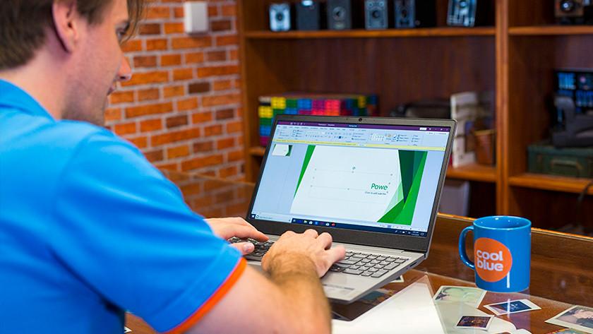 Man werkt aan presentatie op laptop met kopje koffie naast hem op tafel.