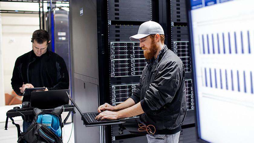 Twee mannen in serverkamer beheren laptops met Windows 10 Pro.