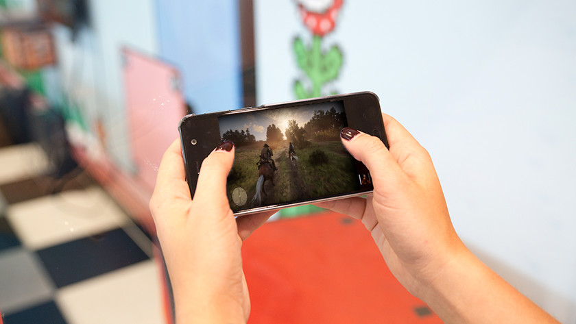 Abeelding van mobiele telefoon waarop Red Dead Redemption gespeeld wordt