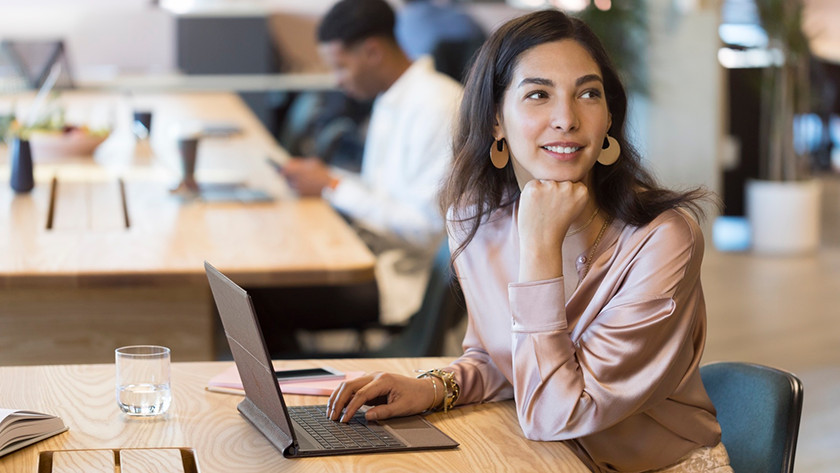 Woman laughs while touching the HP Spectre Folio keyboard with one hand.