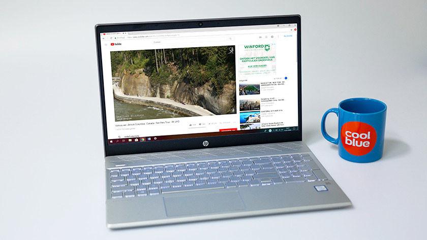 HP Pavilion 15-cs opengeklapt met YouTube op het beeldscherm en Coolblue koffiemok