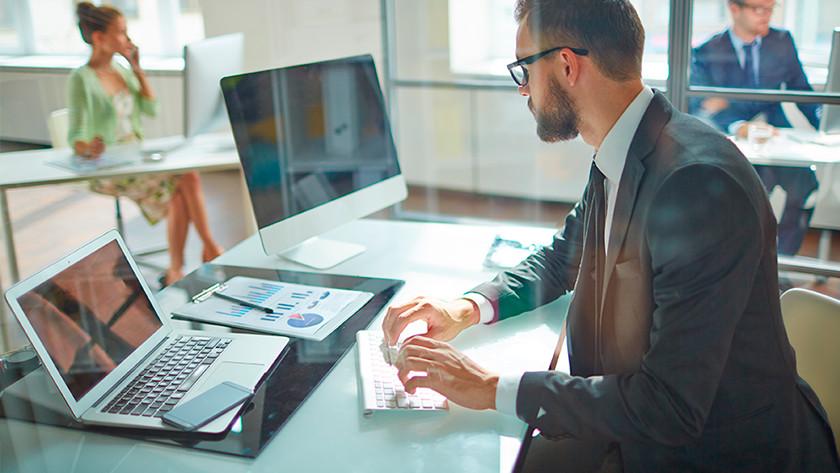 Man op kantoor werkt achter zijn werkplek met een laptop en toetsenbord.
