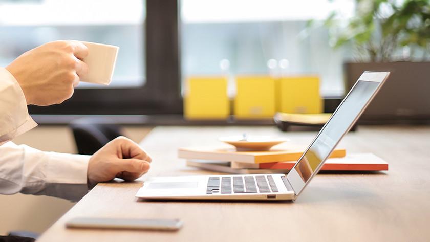 MacBook et une main avec une tasse à expresso.