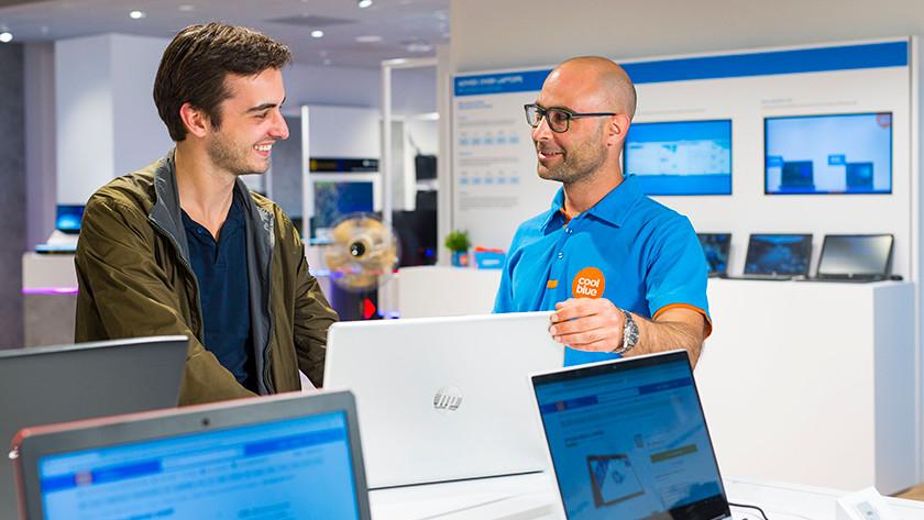 Coolblue medewerker toont HP laptop in winkel Den Haag aan klant.