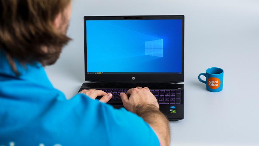 Man werkt achter HP Windows laptop.