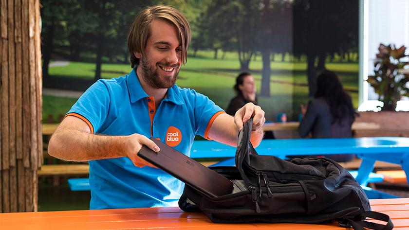 Man stopt laptop in zijn rugzak.
