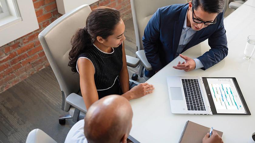Zakelijke man en vrouw kijken op platte HP laptop met Office.