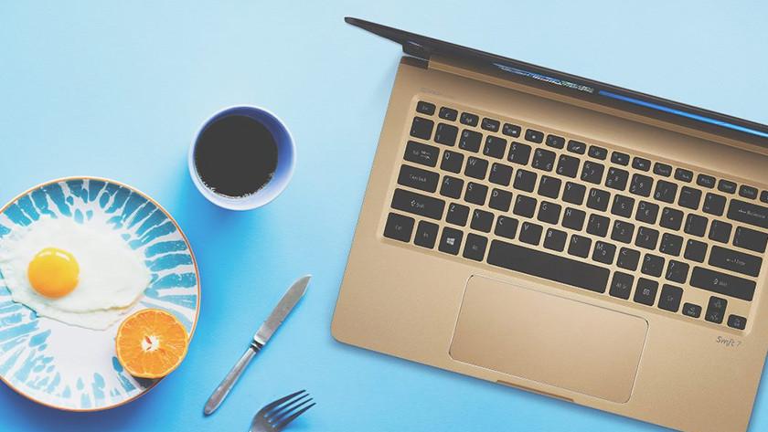 Acer Swift 7 sur une table avec un petit-déjeuner sain à côté.