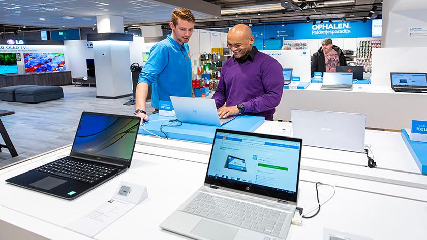 Le client essaie un ordinateur portable dans le magasin Coolblue pendant que l'employé regarde.