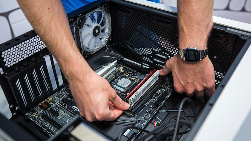 Un homme met de la RAM dans un PC.