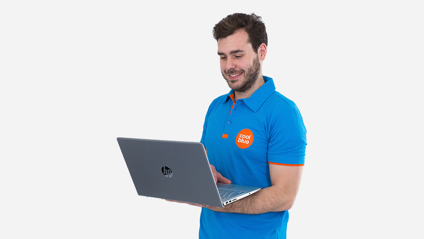 Un homme joyeux avec un ordinateur portable sous le bras.