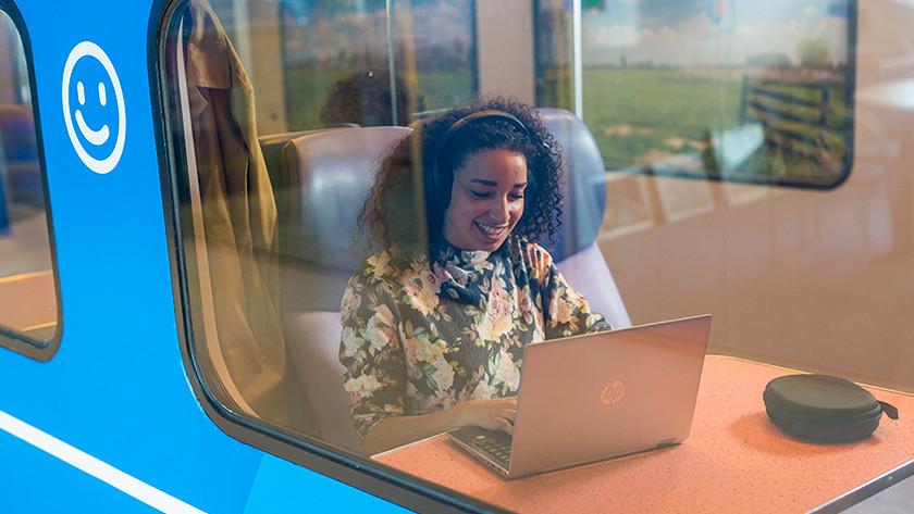 Vrouw in de trein met laptop