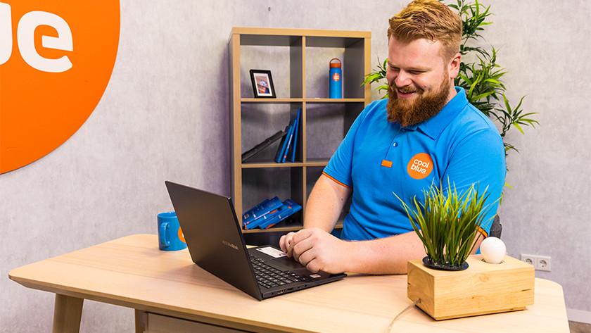 Man gebruik Asus laptop op bureau.