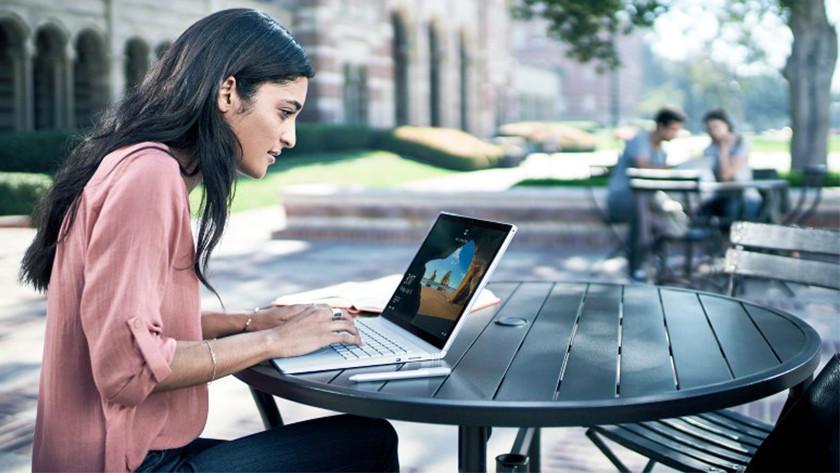 Une femme travaille derrière un ordinateur portable sur la terrasse.