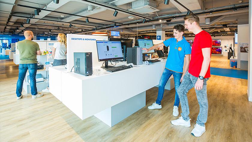 Coolblue medewerker vertelt klant over pc en monitor op winkelmeubel met andere klanten op de achtergrond.