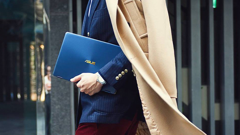 Businessman with a long coat takes Asus ZenBook under his arm.