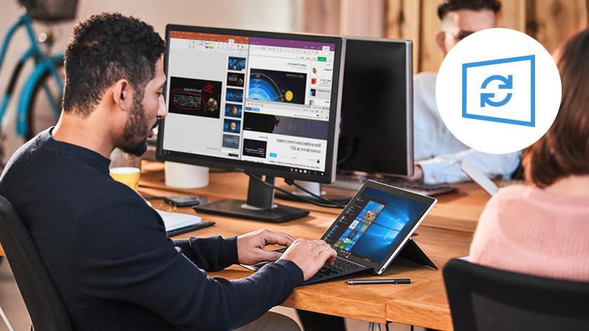 Man werkt met Windows 2-in-1 laptop op kantoor. Windows Update logo in de rechter bovenhoek.