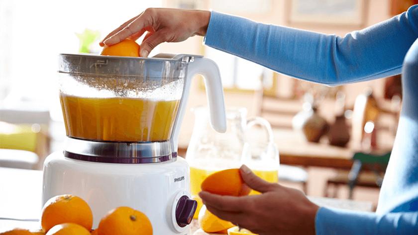 Witte, kunststof foodprocessor met sinaasappelsap