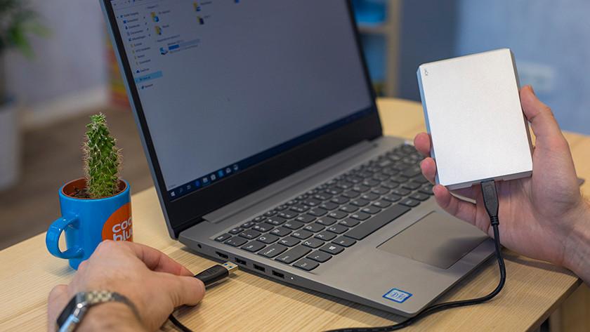 Man sluit LaCie externe harde schijf aan op laptop