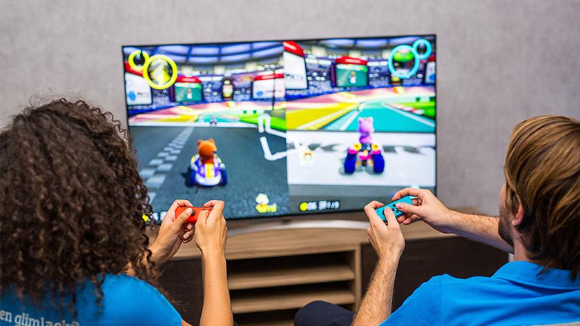 Boy and girl play Mario Kart on the Nintendo Switch.