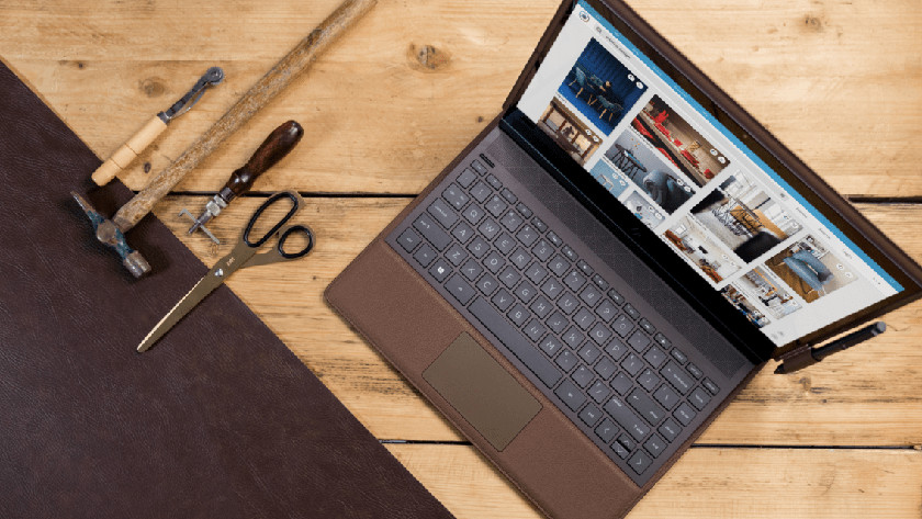 An HP Spectre Folio on a table with tools next to it.