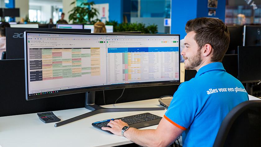 Zakenman werkt op twee monitoren.