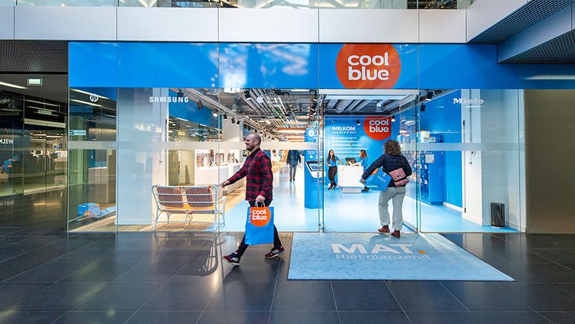 Un homme avec un sac Coolblue quitte le magasin Coolblue après l'achat.