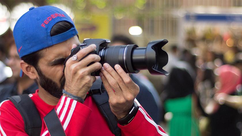 Man met rode trui en blauwe pet maakt foto met camera.