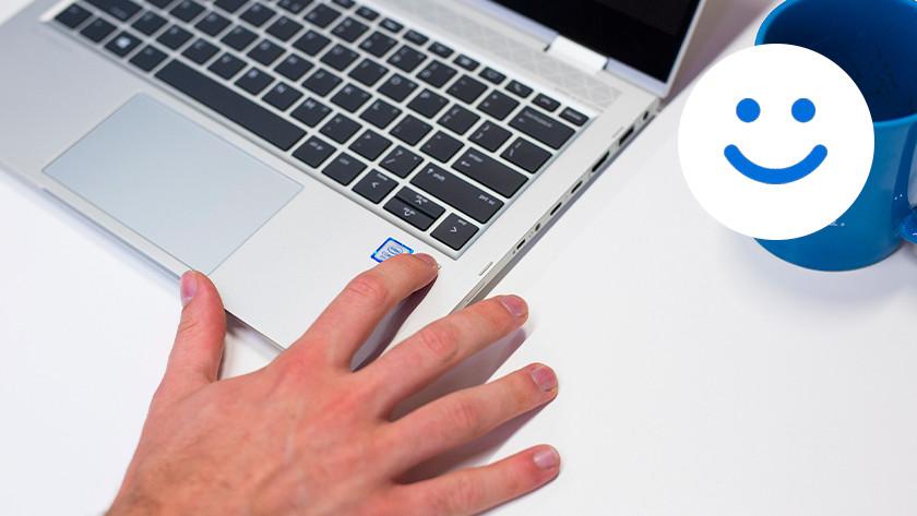 Mannenhand logt in via vingerafdrukscanner van laptop. Windows Hello logo in de rechter bovenhoek.