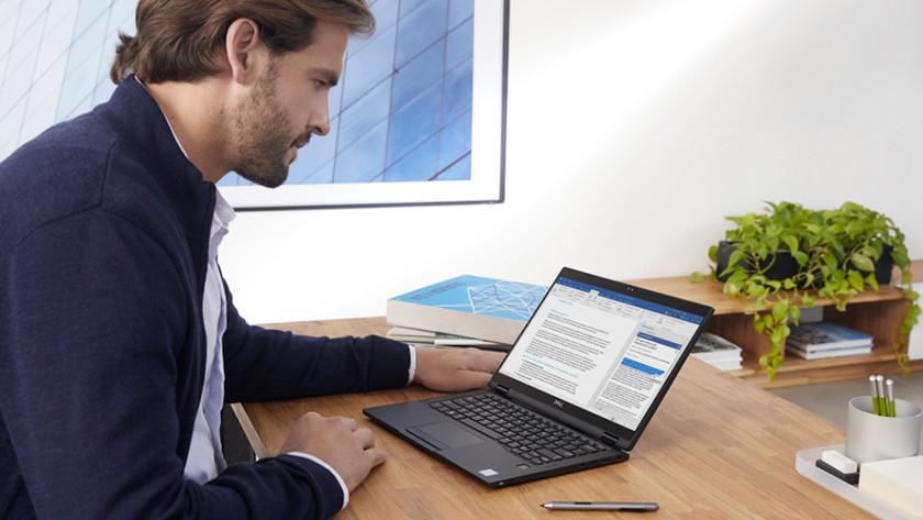Un homme travaille sur un ordinateur portable avec Windows 10 Pro.