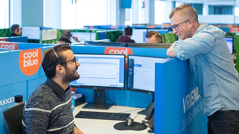 Twee mannen van de Coolblue klantenservice praten met elkaar.