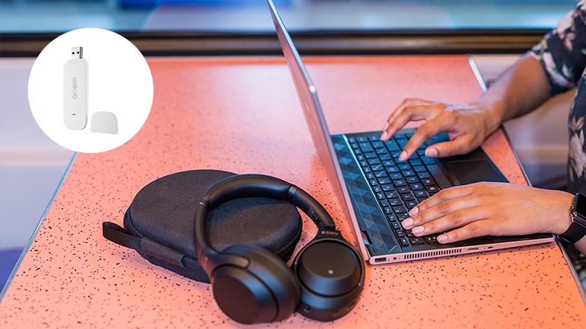 Laptop en koptelefoon op treintafeltje.