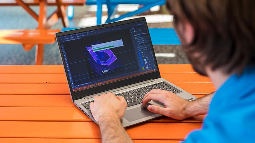 Man bewerkt foto's in Photoshop achter laptop.