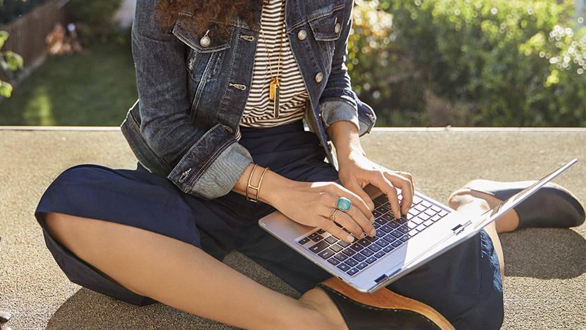 Vrouw zit buiten in de zon op balkon en gebruikt Chromebook om op te werken.
