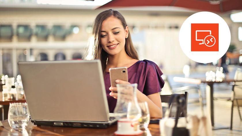 Femme sur la terrasse regarde son téléphone avec un ordinateur portable sur la table en face d'elle. Un logo Remote Desktop dans le coin supérieur droit.